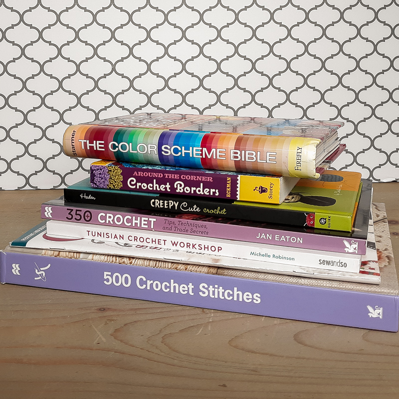 Stack of crochet stitch books on a neutral wood table