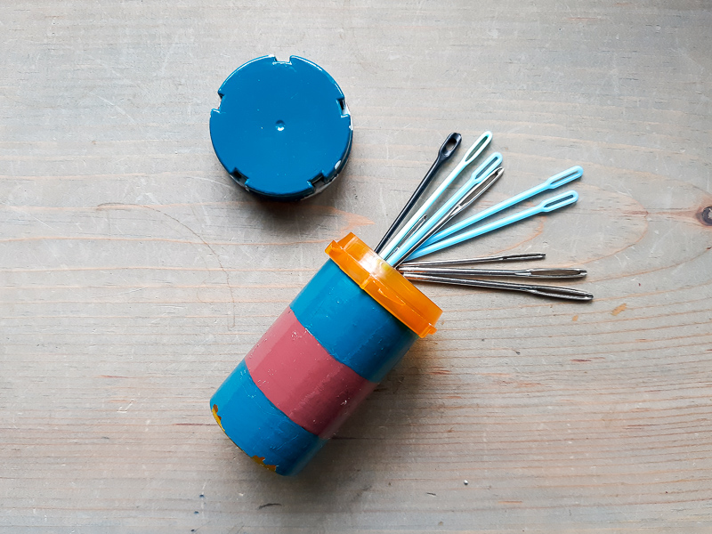 Metal and Plastic Darning needles spilling out of a painted prescription bottle on a neutral wood background
