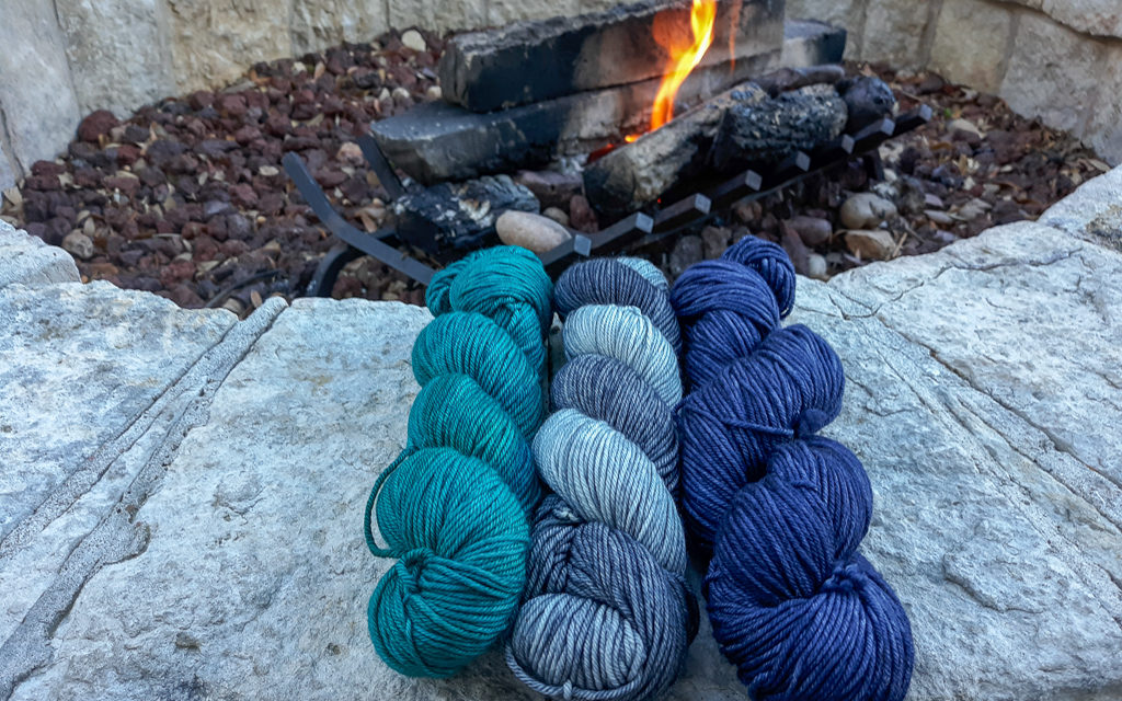 3 hanks of yarn displayed on stone with a firepit in the background