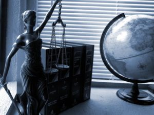 workers comp law books on table with globe and justice figure