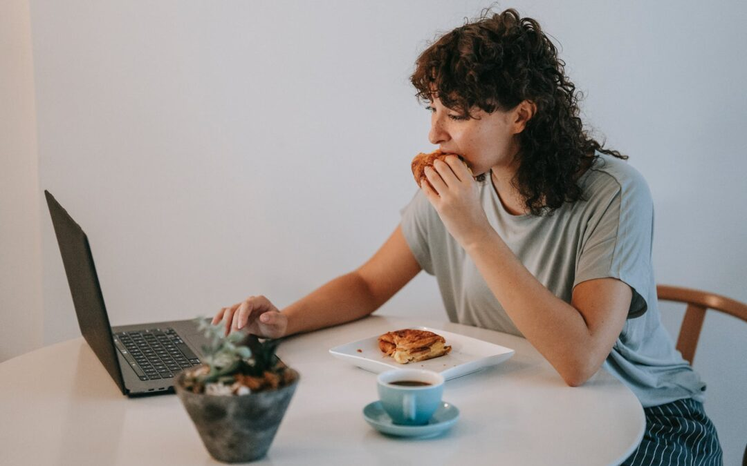 young woman eating breakfast toasts and using laptop