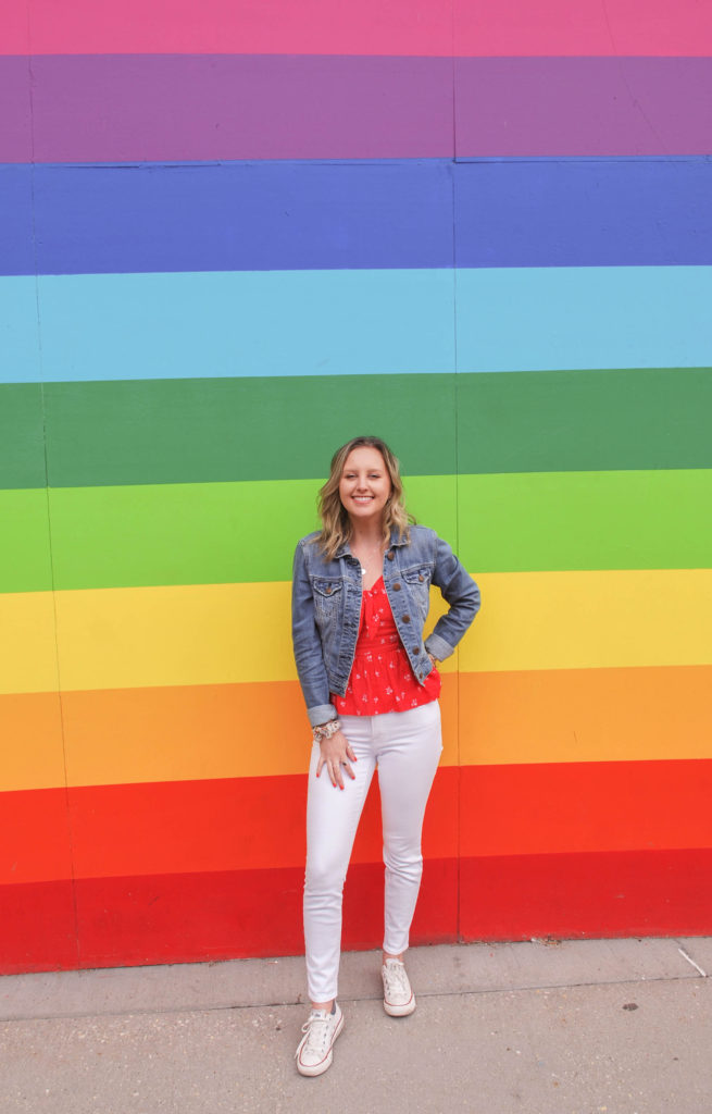 Blonde Woman Supporting White Jeans in front of a Rainbow Wall Mural in Chicago, IL