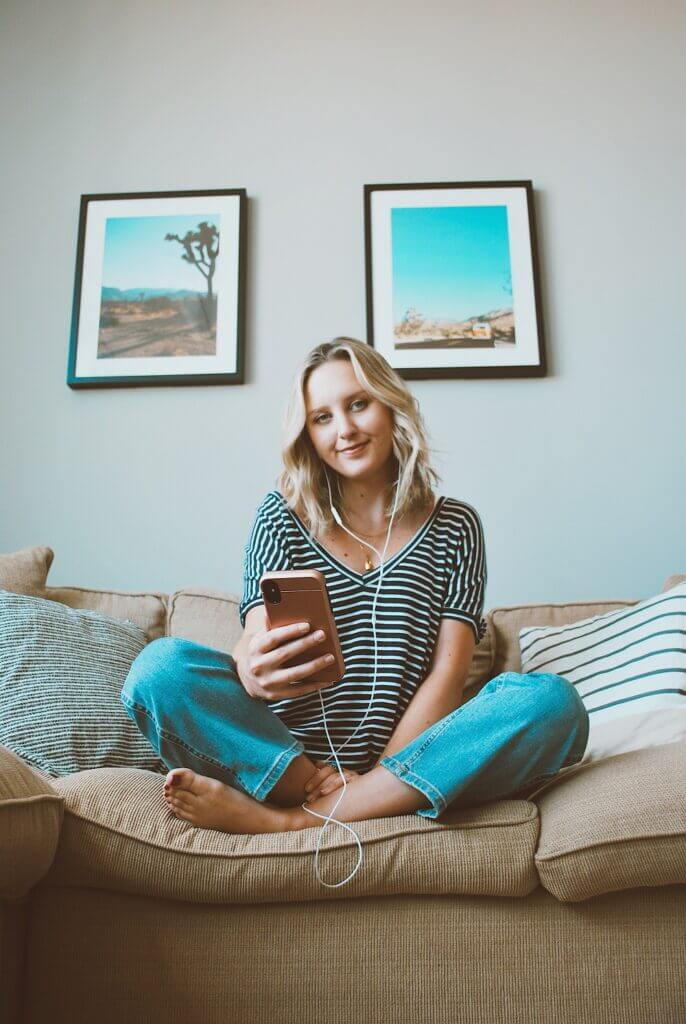 Blonde woman listening to a podcast on the couch