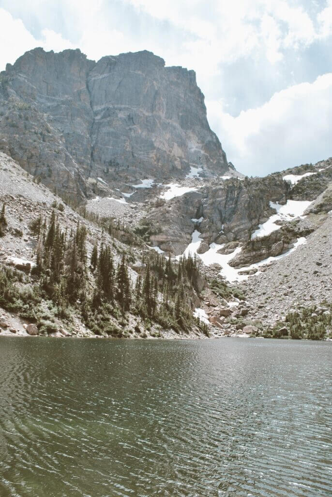 Mountains towering over the crystal clear Emerald Lake in rmnp
