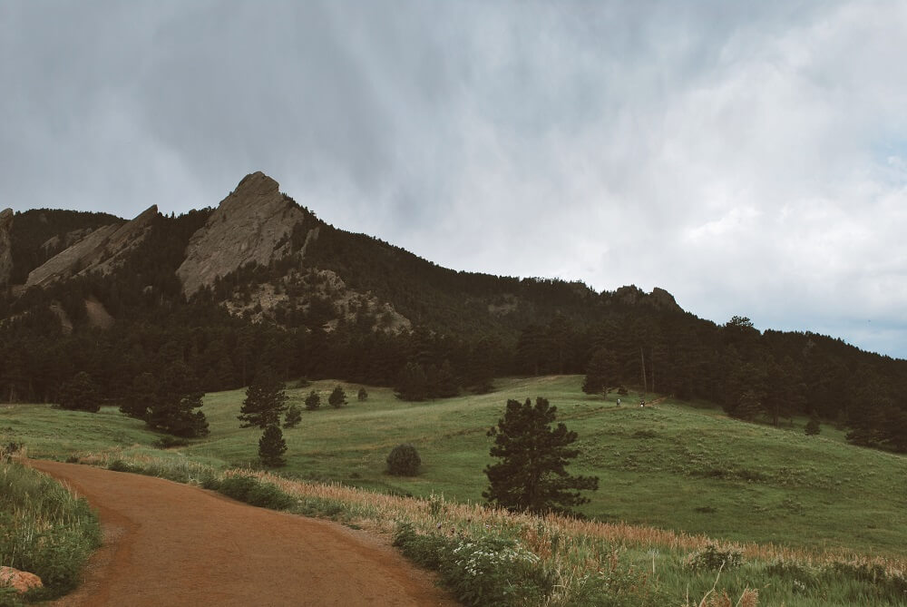 The Flatirons in the distance of Boulder, CO covered in trees