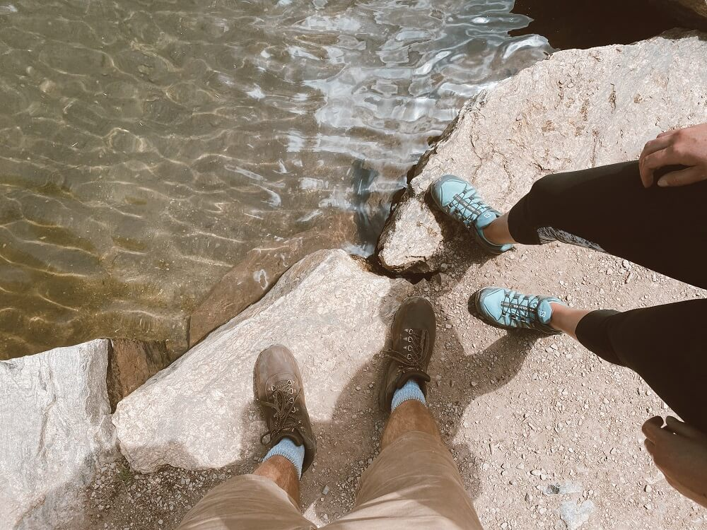 Hiking shoes next to a clear water lake in the Rocky mountains