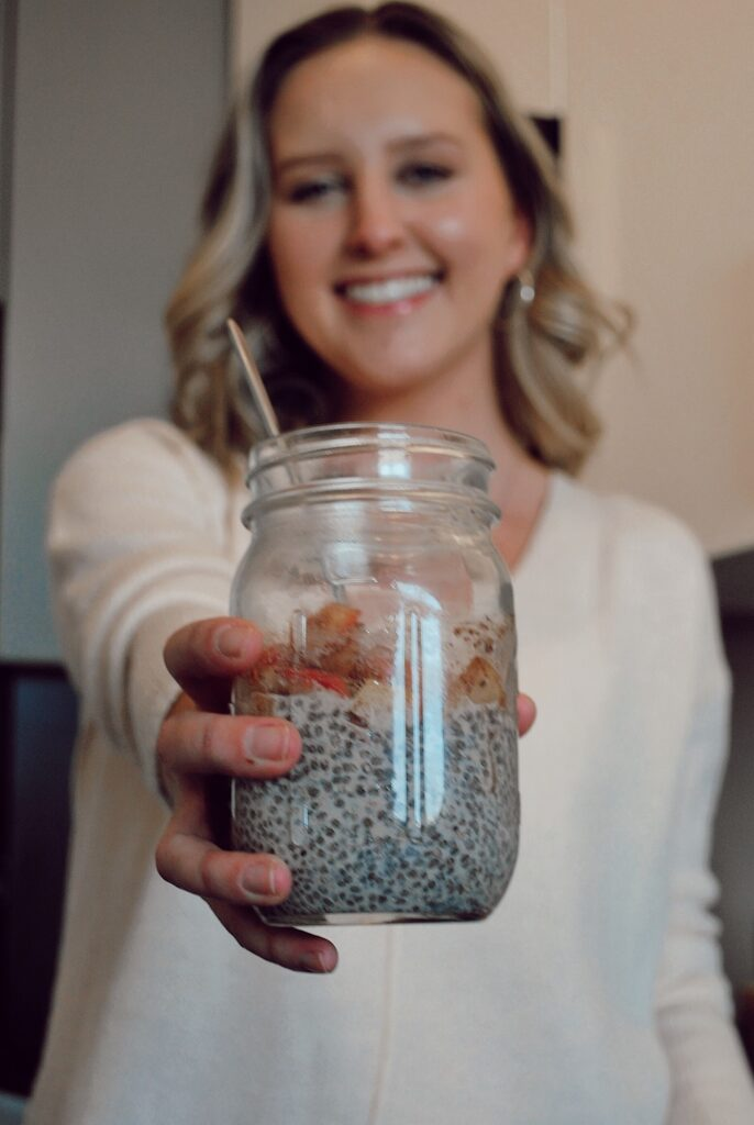 Mason jar full of chia seed pudding with a warm cinnamon apple topping