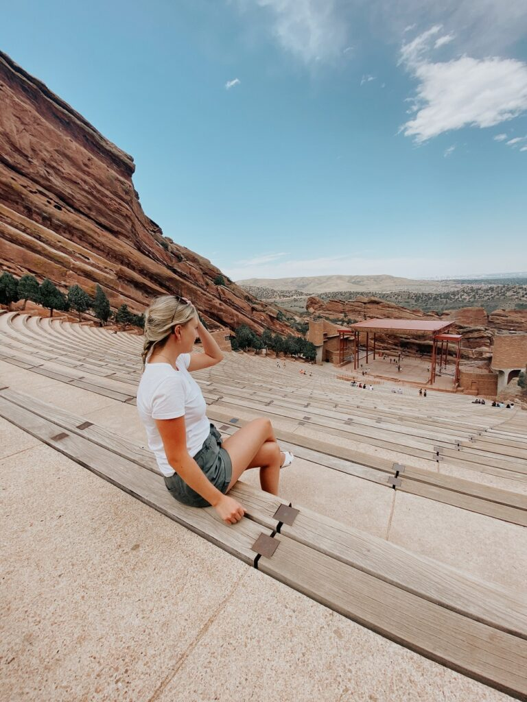 Woman sitting at an empty red rocks theater in 2020