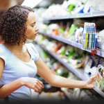 grocery shopper looking at pre-packaged produce
