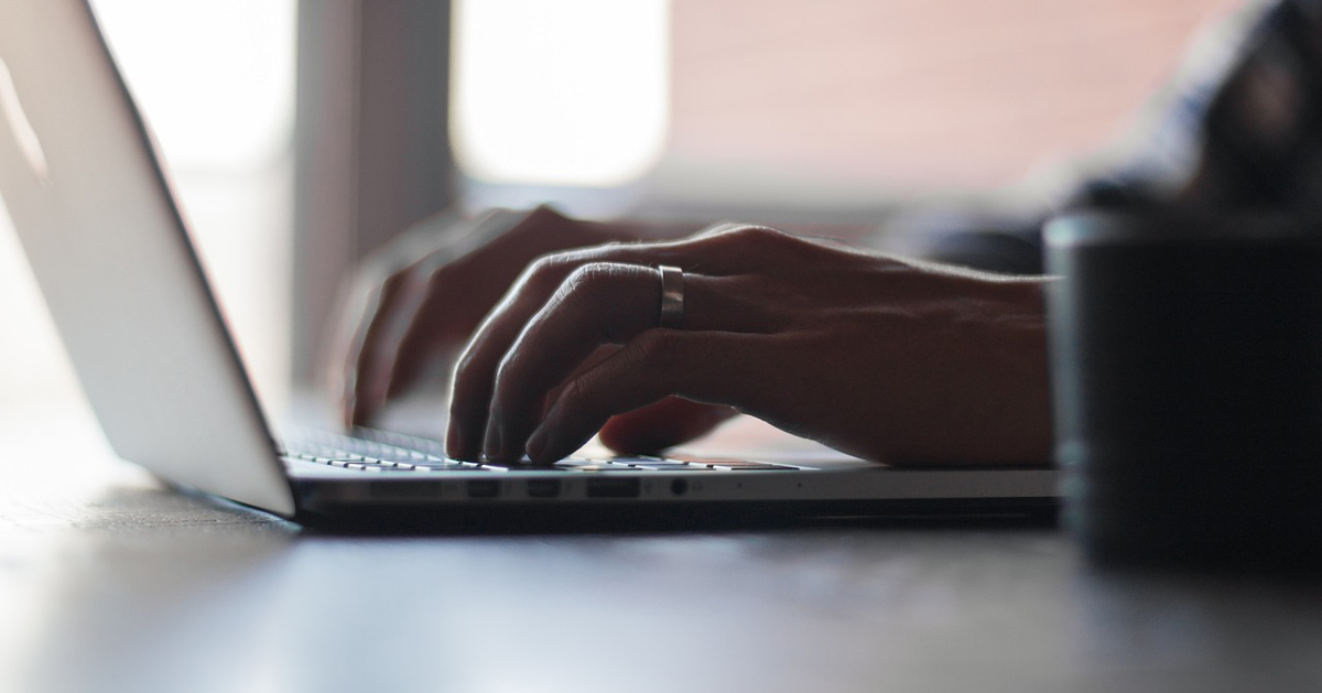 Person typing on laptop, close-up of hands.