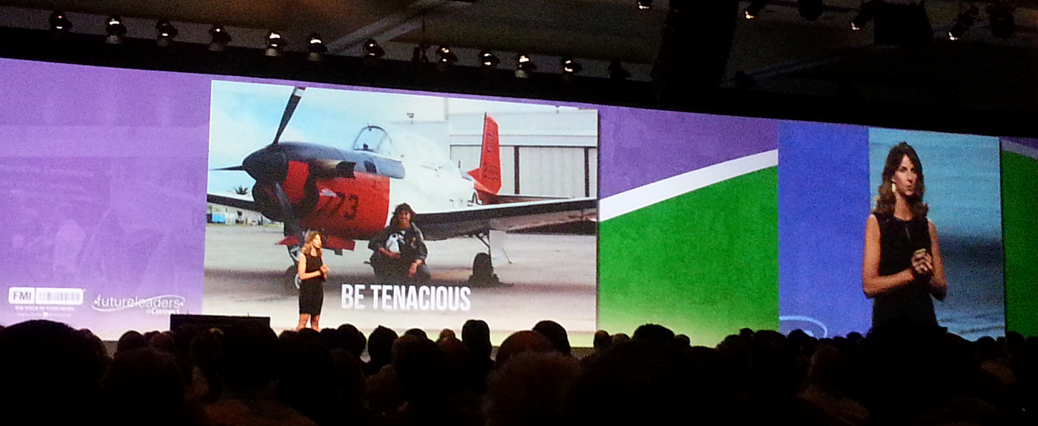 Presenter on stage with slide saying Be Tenacious behind her.
