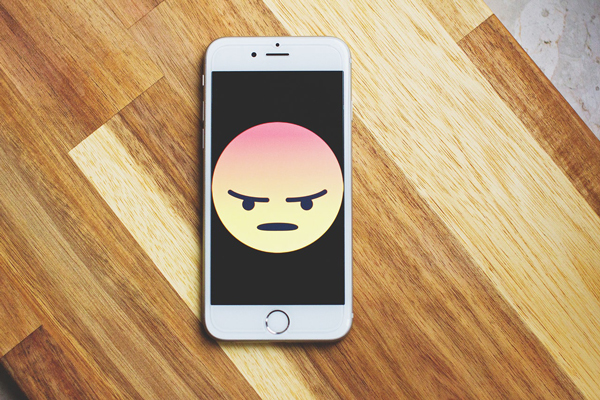 angry emoji, smart phone, wooden table