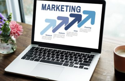 laptop on desk, marketing presentation on screen