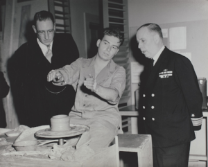 A war veteran talking to Admiral Monroe Kelly (right) about his pottery work.