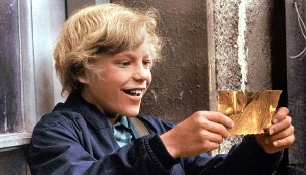 Charlie with his golden ticket in Willy Wonka and the Chocolate Factory. Via roalddahl.fandom.com.