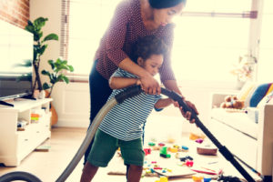 Mom Vacuuming with Child Home Cleaning in Cypress