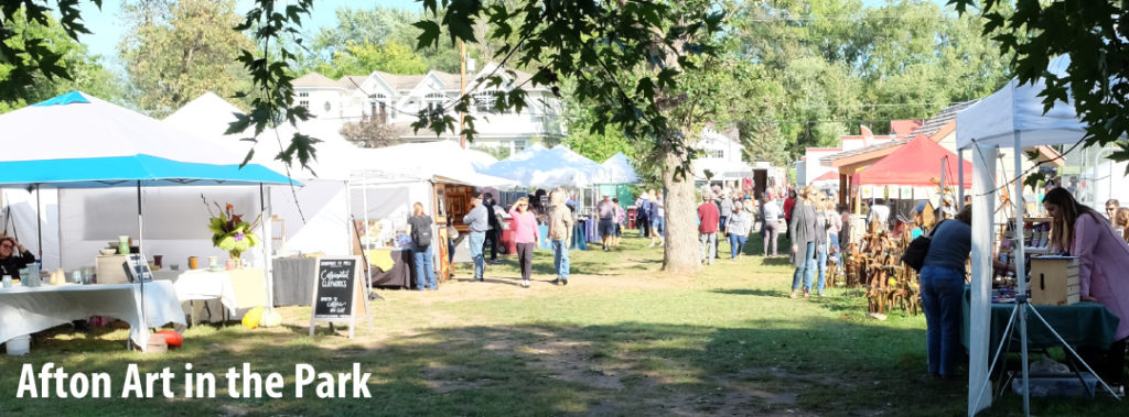 Fall art fair image with tents full of artwork and fine crafts. Shoppers are walking along tents on a sunny day.