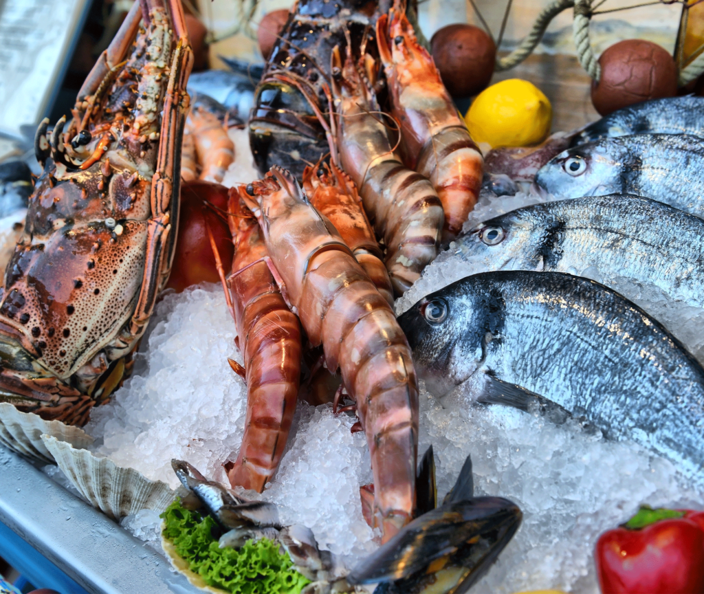 An assortment of seafood resting in ice as part of a outdoor market display