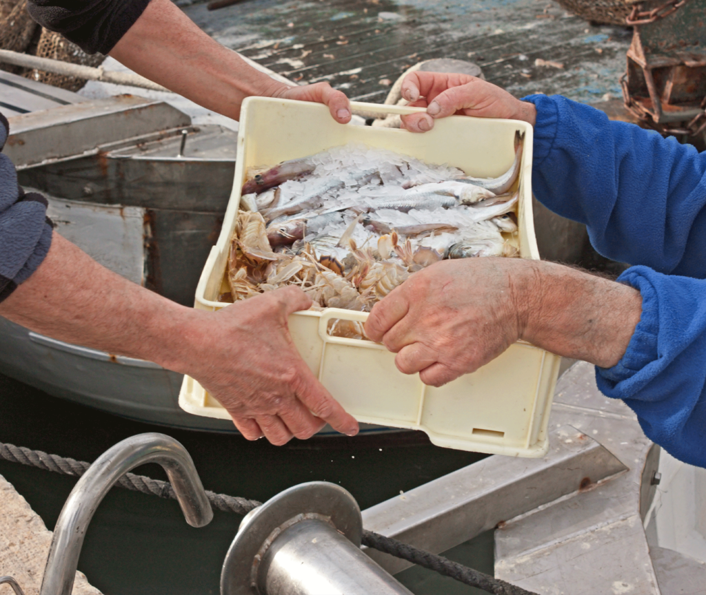 Man handing a box of assorted seafood to another man