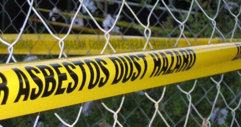 yellow tape on a chicken wire that says ASBESTOS DUST HAZARD