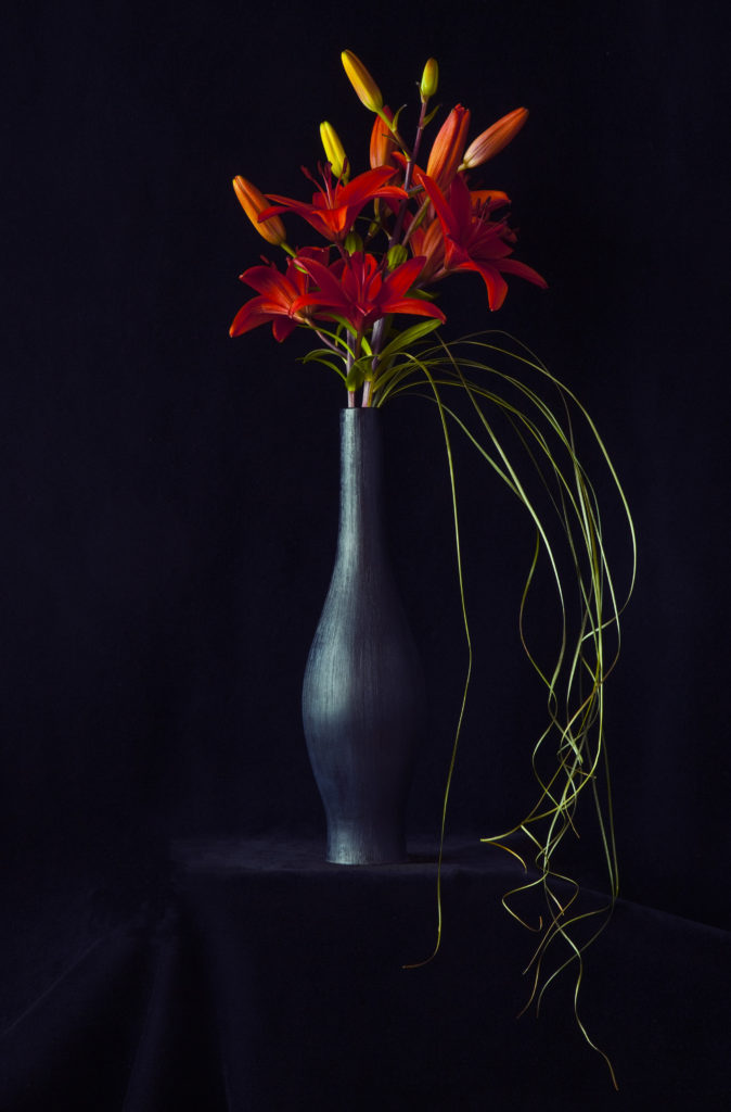 Red Asiatic Lilies in a Black Vase