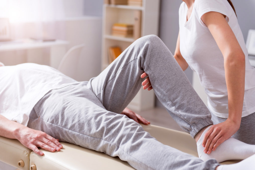 Treatment. Cropped image of male patient lying down with female physiotherapist performing some stretch exercises on mans leg