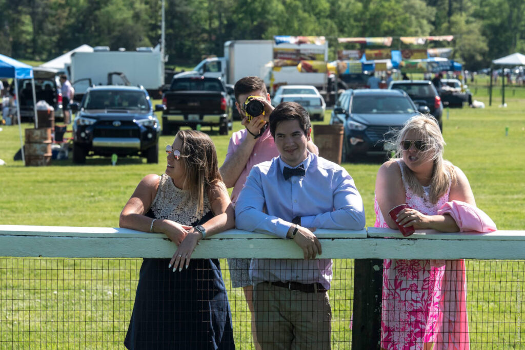 Well-Dressed onlookers lean on the track railing at Foxfield