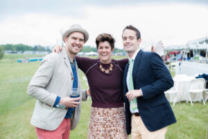 Three well-dressed people pose for a photo at the Foxfield Races