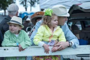 Man with young boy and girl leaning on the track railing wearing fancy clothes at Foxfield