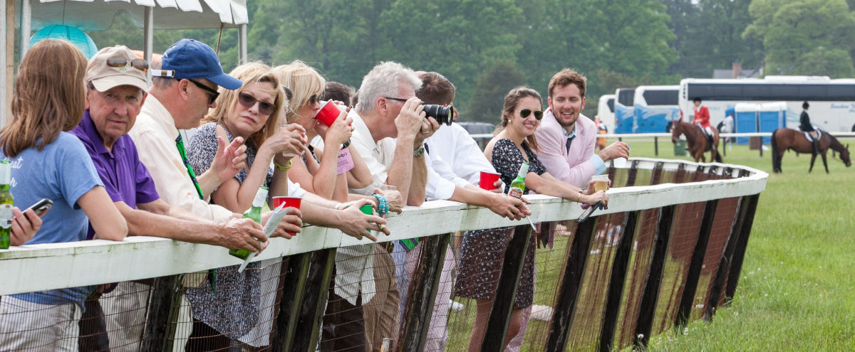 Crowd leaning on the rail watching the races at Foxfield