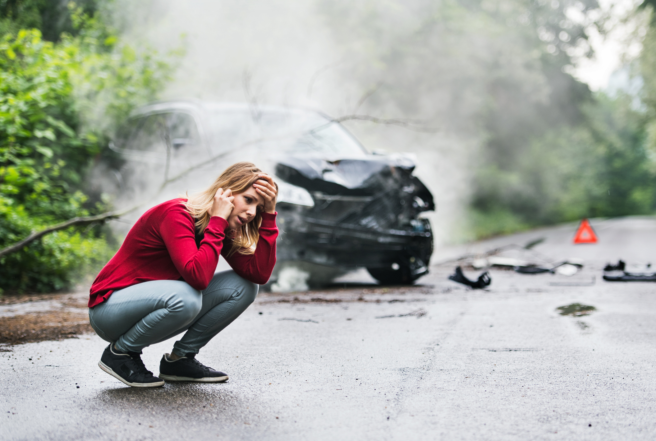 A frustrated young woman with smartphone by the damaged car after a car accident, making a phone call. Copy space.