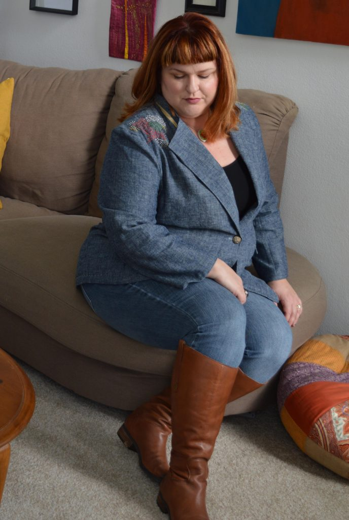Woman sitting in a living room wearing a blue blazer with embroidered shoulders