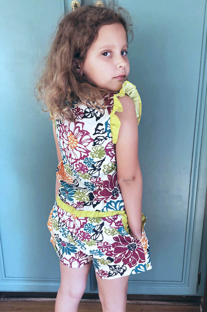 Image of a young child looking over her shoulder with a floral jumpsuit with a lime green waist band and shoulder ruffle standing in font of a blue green cabinet doors.