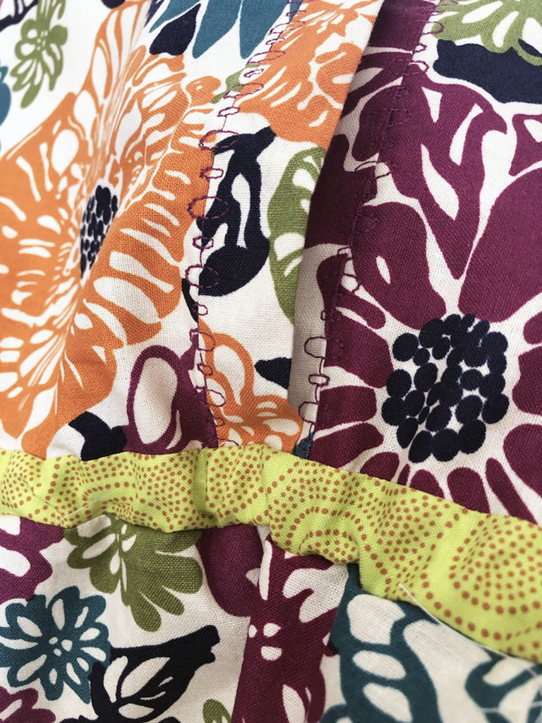 Close up image of a front button placket with bubble machine embroidery stitches and lime green waistband