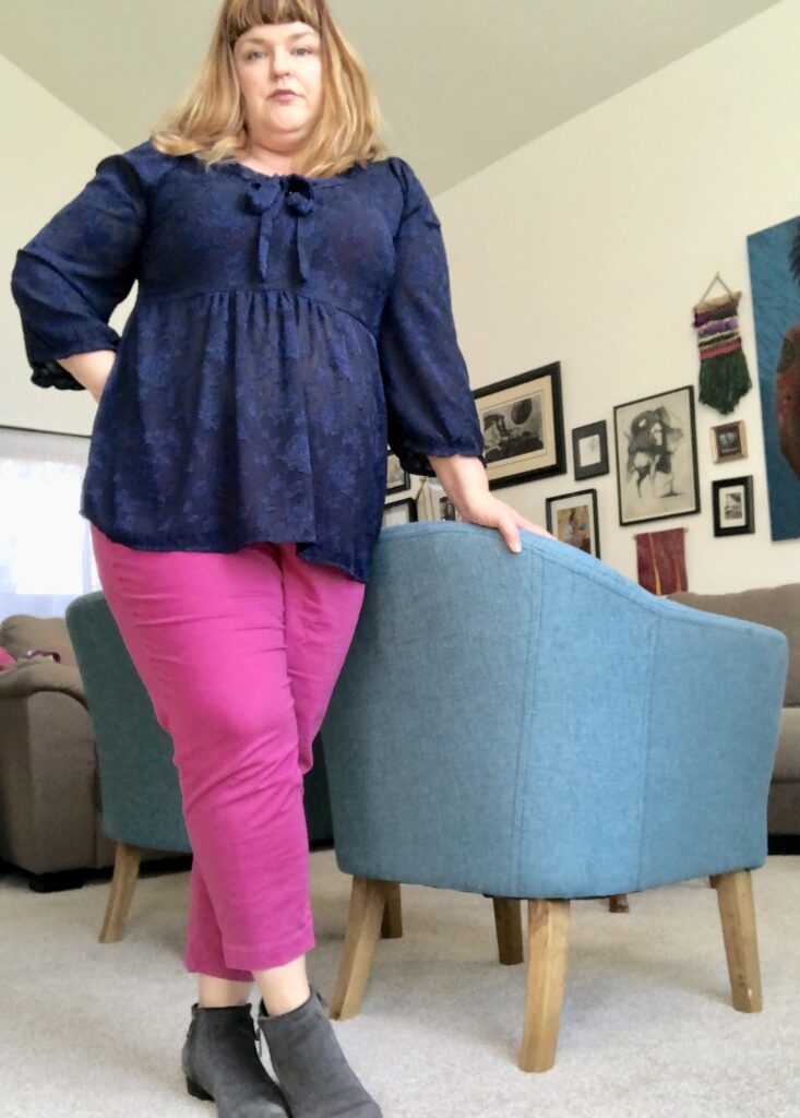 Lauren standing staring at the camera with one hand on her hip and another resting on a chair with navy long sleeved top, hot pink skinny pants and grey boots.