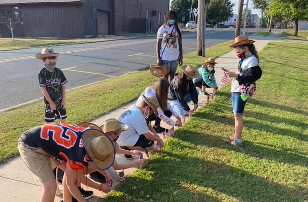 Brunson students place flags at the Y in honor of the lives lost during September 11 and the war that followed