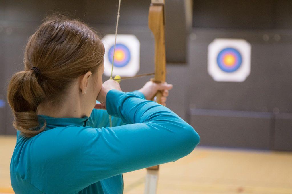 Girl shooting arrow at target