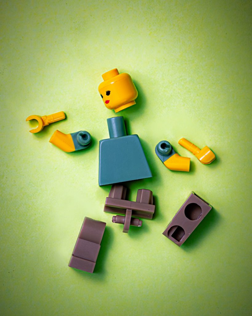 Lego figure in pieces representing breaking problems down into first principles