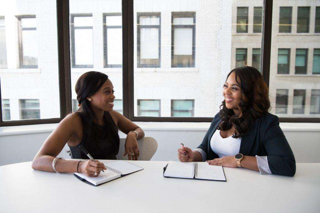 Two women talking in an office.