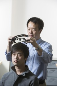 Brainprint: Zhanpeng Jin, assistant professor of Electrical and Computer Engineering and Biomedical Engineering uses an electroencephalogram headset to measure electrical signals within the brain, on Binghamton doctoral student Borui Li. (Jonathan Cohen, Binghamton University photographer)