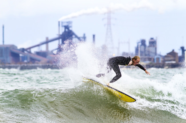 Surfers: A surfer rides a wave against the industrial backdrop of Lake Michigan. (Credit: Mike Killion/Courtesy of Surfrider)
