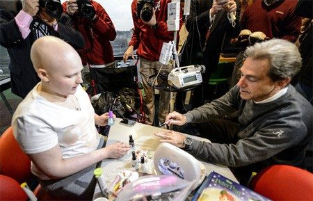 Alabama head coach Nick Saban lets Gabrielle Nave paint his nails.