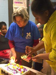 Early days of Eastport Girls Club … co-founder Helena Hunter and EGCer prepare birthday cake celebration