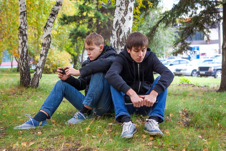teenage boys sitting under tree