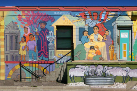 """The mural on Trinity's building at 20th and Riverside Is filled with biblical figures. The artist, Larry Rostad, wrote: """"We have represented the extended family of faith with paint, in mural form …. Our hope is that Trinity's mural will contribute to our neighborhood; may visible hand-painted images help reveal the INVISIBLE things of the Spirit."""""""
