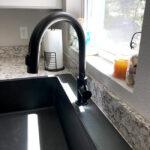 black quartz kitchen sink and black faucet