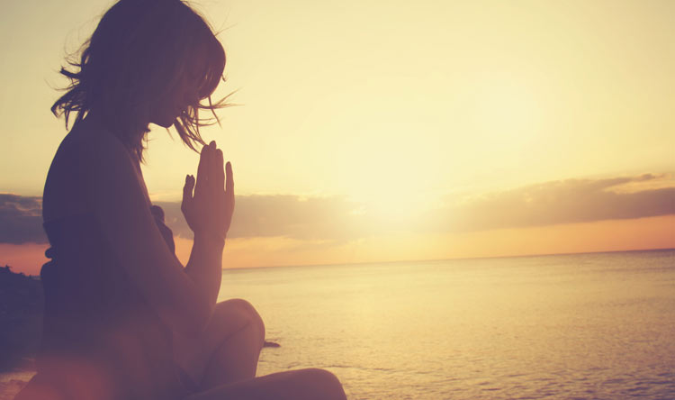 mindfulness meditation by the ocean with a sunset