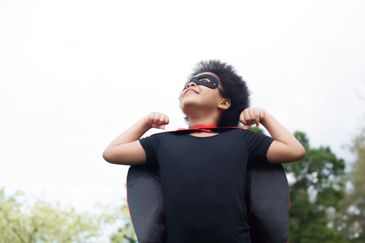 child flexing superhero