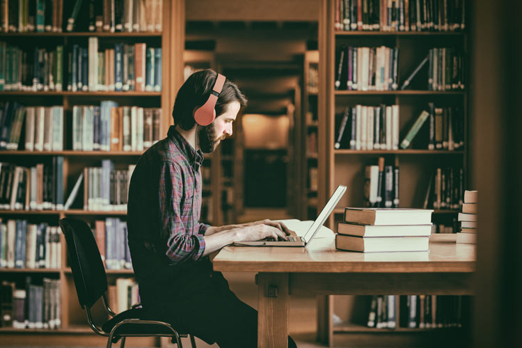 Smart man studying at a library