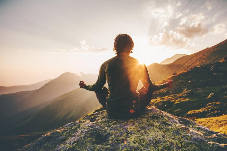 Hiker meditating on a mountain